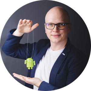 Martin Doudera, the Android developer and owner of the app, holding his Android plastic figurine on a string above his palm. That figurine sits daily on his work desk